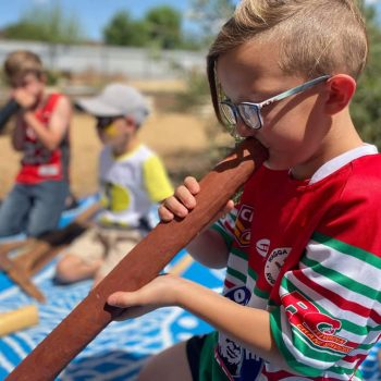 local boy playing didgeridoo at Ashmont Re-Opening Event